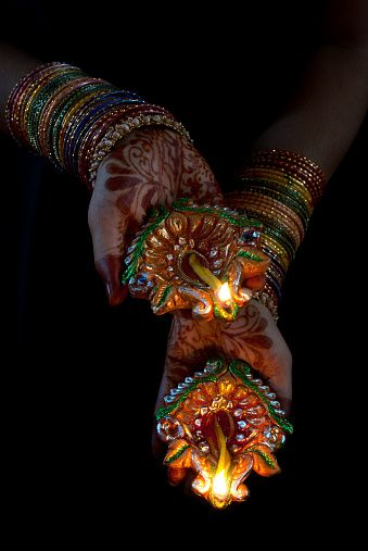 Colorful hands with Mehendi holding earthen lamps during Diwali Festival,India.