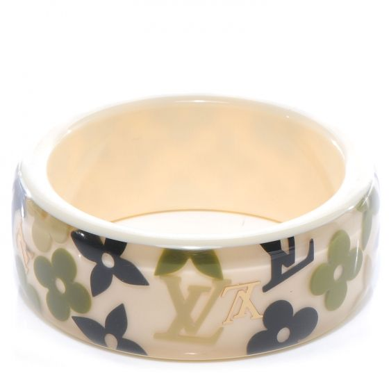 This is an authentic LOUIS VUITTON Farandole Bracelet in Ivory.   This is an elegant and unique bracelet crafted of an ivory ground with clear resin with black khaki and brass symbols from the Louis Vuitton monogram suspended in the resin.