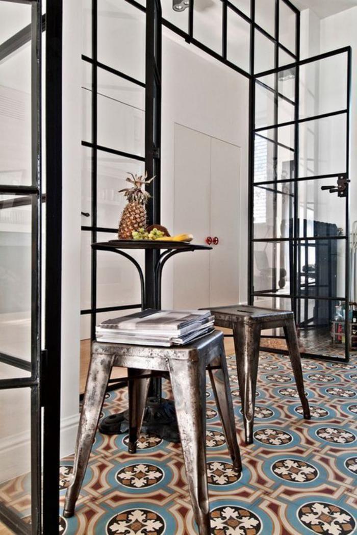 carreaux de ciment, grande porte vitrée et tabourets métalliques