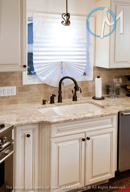 Colonial Gold set against the white cabinets creates a low-contrast combination that works.
