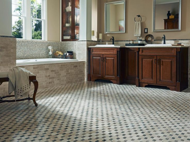 A mosaic tile floor adds depth to this traditional bathroom. A tile tub surround enhances the room's luxurious feel, while dual wood vanities and a cabinet above the tub provide plenty of storage space.