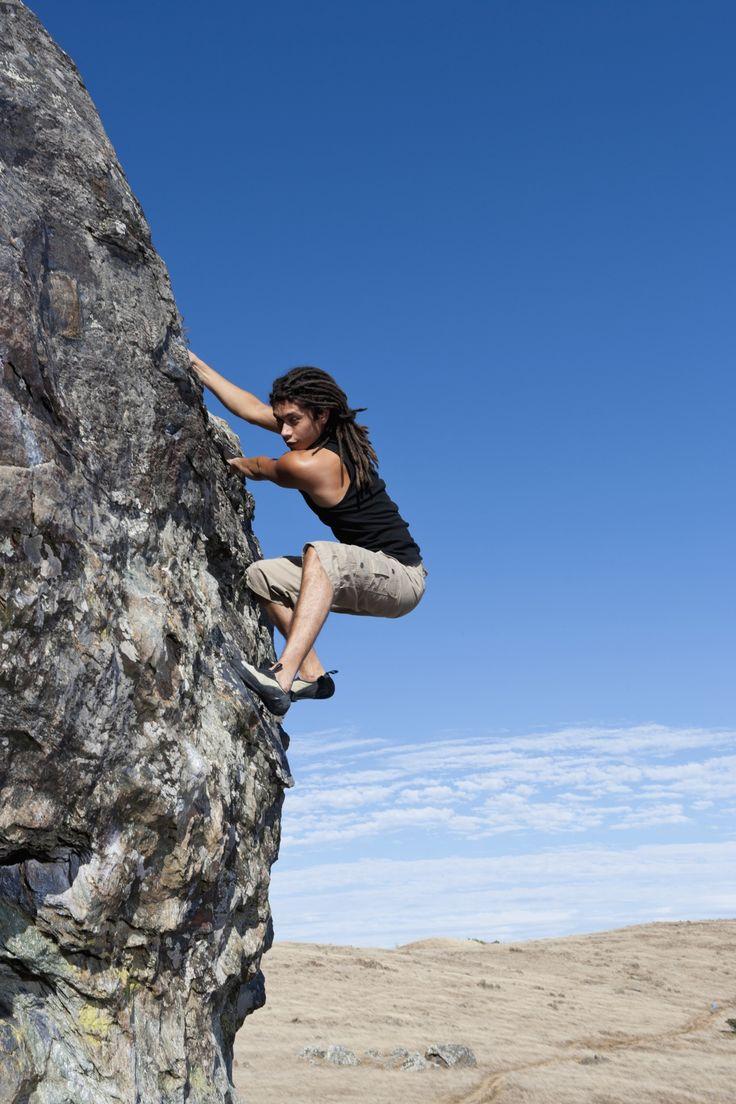 Hispanic climber scaling steep rock face - Hispanic climber scaling steep rock…