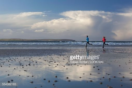 Young couple running at beach, Dunnet Bay, Caithness, Scotland, United Kingdom