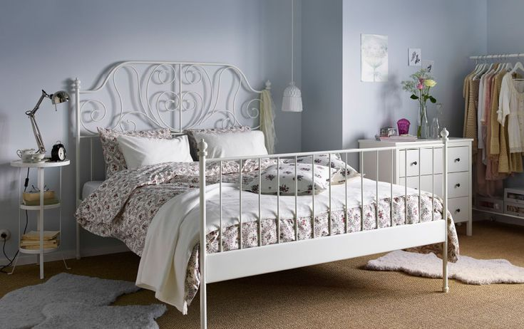 A white steel bed with bed textiles in white and with floral patterns.