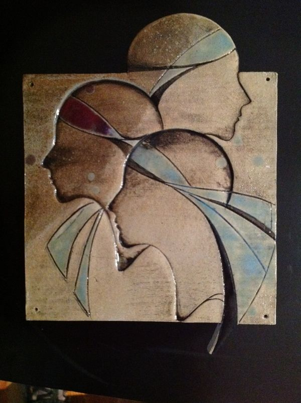 Ceramic wall piece w multi face imprints glazed