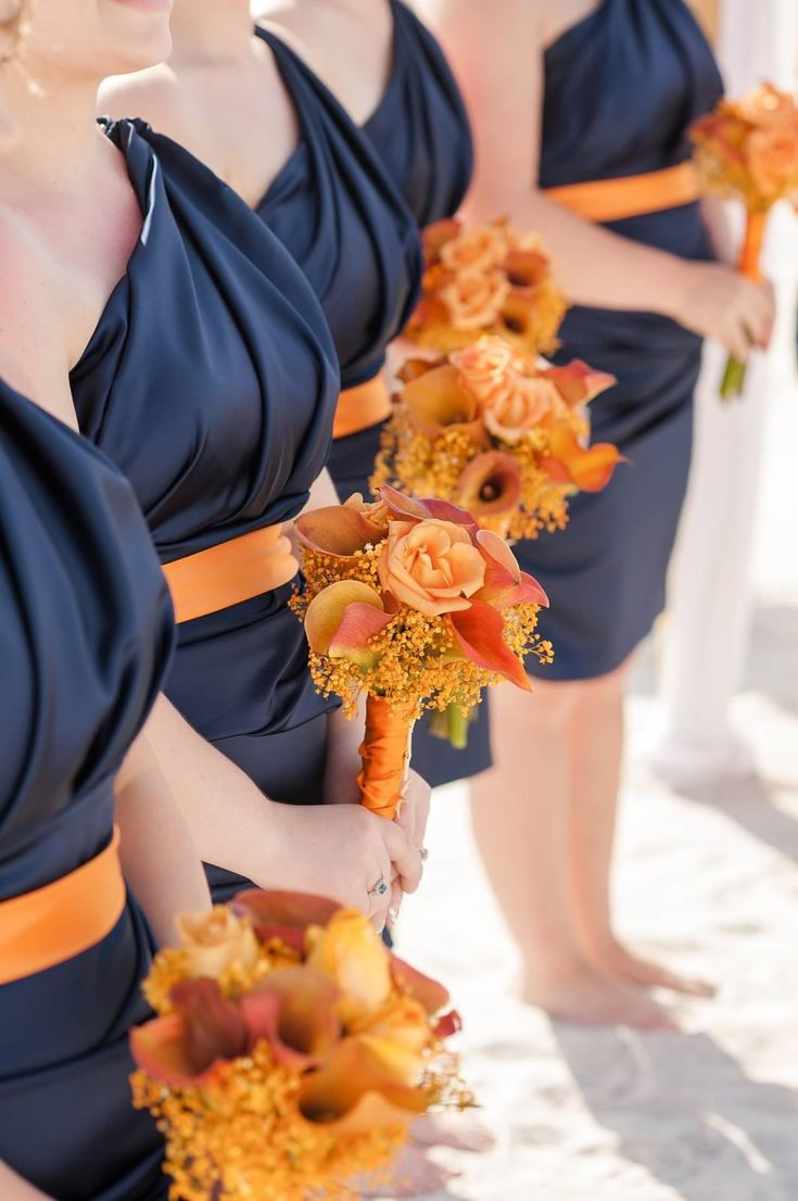 Uniform bridesmaids dresses. Cute color combo for fall. TIP: If you have two theme colors, get the bridesmaids dresses in a dark color and add your second color as a belt and accent with flowers. Like this blue and orange combo