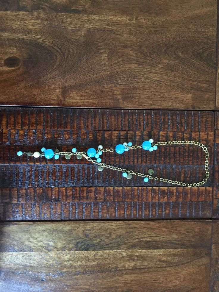 Big blue beads strung asymmetrically with pearls and translucent blue bead dangles on bronze chain