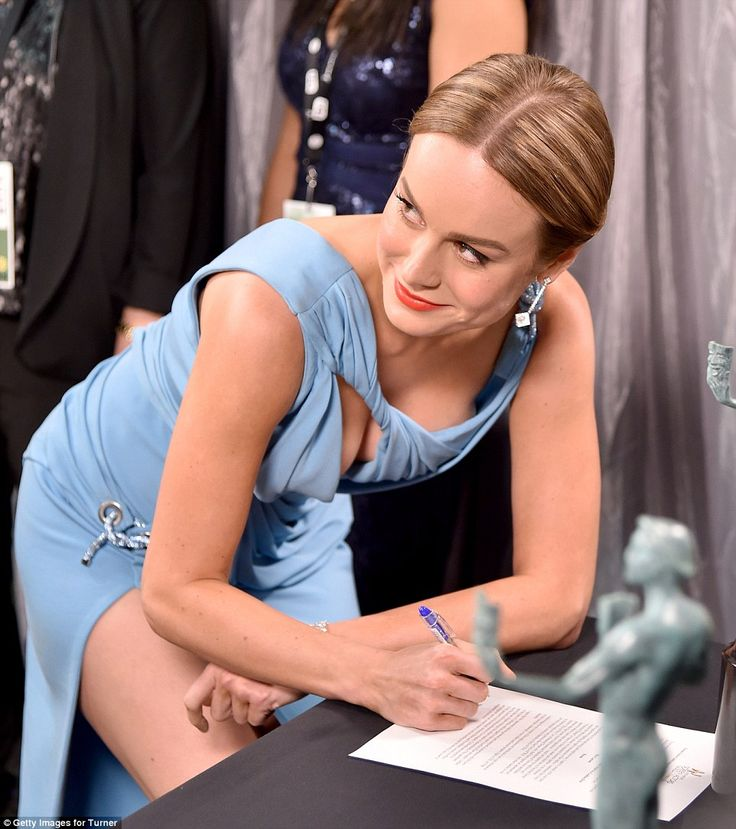 Bold move: Brie Larson gave onlookers an eyeful as she bent down to sign a document...