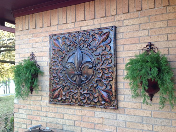 Fleur D Lis metal art bought @ Hobby Lobby for 50% off. Metal Wall Sconces found @ Garden Ridge, I spray painted them to match. Artificial Asparagus Fern from Hobby Lobby. I used 40% off coupon. It added color to a one colored brick wall.: