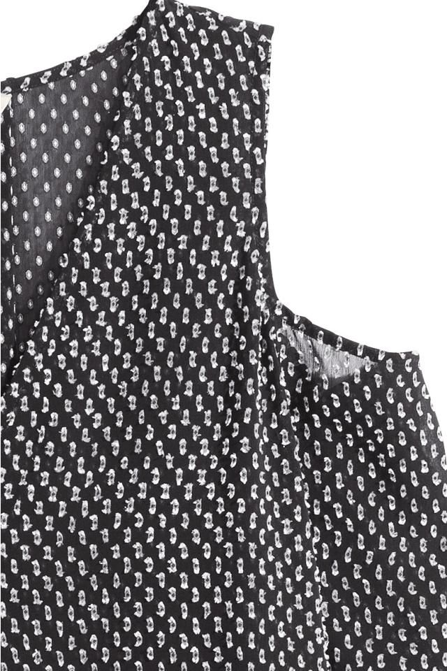 Blouse transparente en mousseline plumetis. Modèle ample avec encolure en V et partie découpée au niveau des épaules. Manches longues terminées par liens à