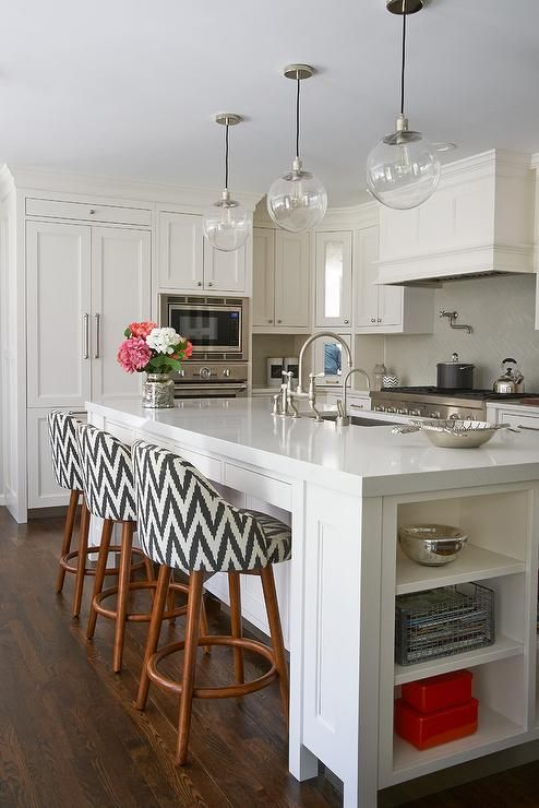 Fabulous kitchen features a long center island fitted with end cookbook shelves topped with Pental Quartz Lattice fitted with a stainless steel sink and deck mount faucet lined with chevron counter stools, West Elm Saddle Barstools, illuminated by three clear glass globe pendants.