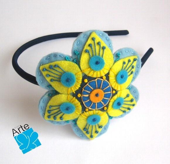 Tiara com mandala em feltro, em formato de flor, detalhadamente bordada. Dimensões: 10,0 cm de diâmetro. Fino acabamento... R$30,00