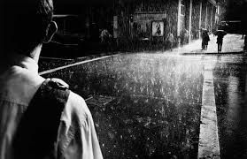 Photo by Trent Parke. This is a great image in the rain on the streets, the sun highlights the rain and I like the framing with the back of the boy about to cross the road, empty road and people running ahead. Like the black and white again