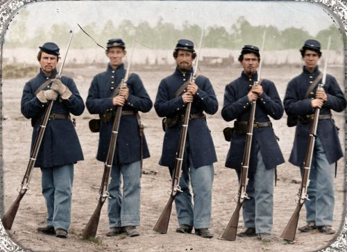 Five soldiers, four unidentified, in Union uniforms of the 6th Regiment Massachusetts Volunteer Militia outfitted with Enfield muskets in front of encampment Source: https://c1.staticflickr.com/9/8799/17678873915_32a9435155_o.jpg