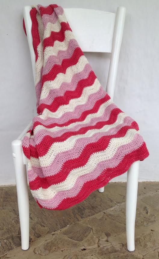 Hand knitted baby ripple pram blanket made of 100% cotton yarn.