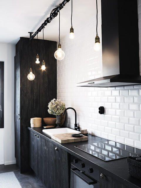 Edison light bulbs against clean white subway tiles and deep black furniture.