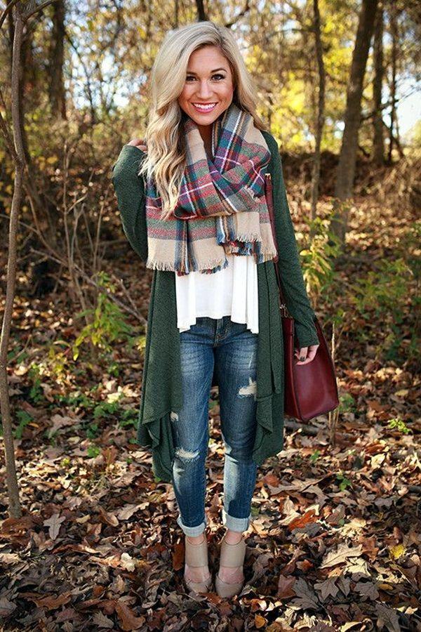 La mujer lleva una bufanda con diferentes colores. La bufanda cuesta quince dólares. Ella también lleva puesta una rebeca verde oscuro. La rebeca cuesta once dólares. Finalmente, ella lleva pantalones vaqueros con botas marrones. Los pantalones vaqueros también cuestan once dólares y las botas cuestan diez dólares.