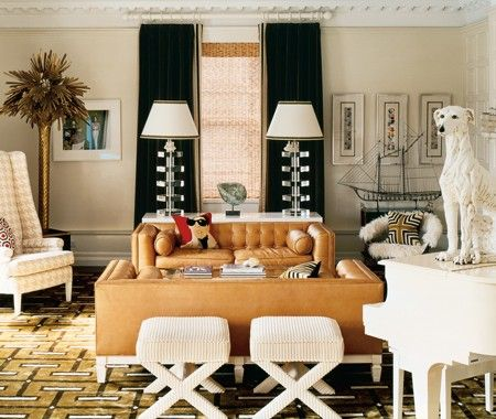 Salon Style Living Room    Tailored and tufted leather sofas exude all-American style.    Crisp details and symmetry — from the drapes to the sofas to the matching lucite table lamps — ground this space decorated by New York designer Jonathan Adler. That restraint allows for whimsical accessories, from the dog sculpture and a houndstooth-upholstered chair to a bronze palm tree.
