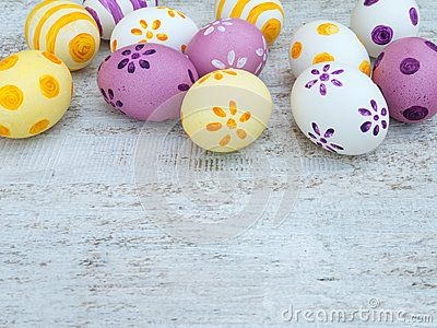 White, violet and yellow easter eggs decorated by stripes, dots and flowers on the white wooden board