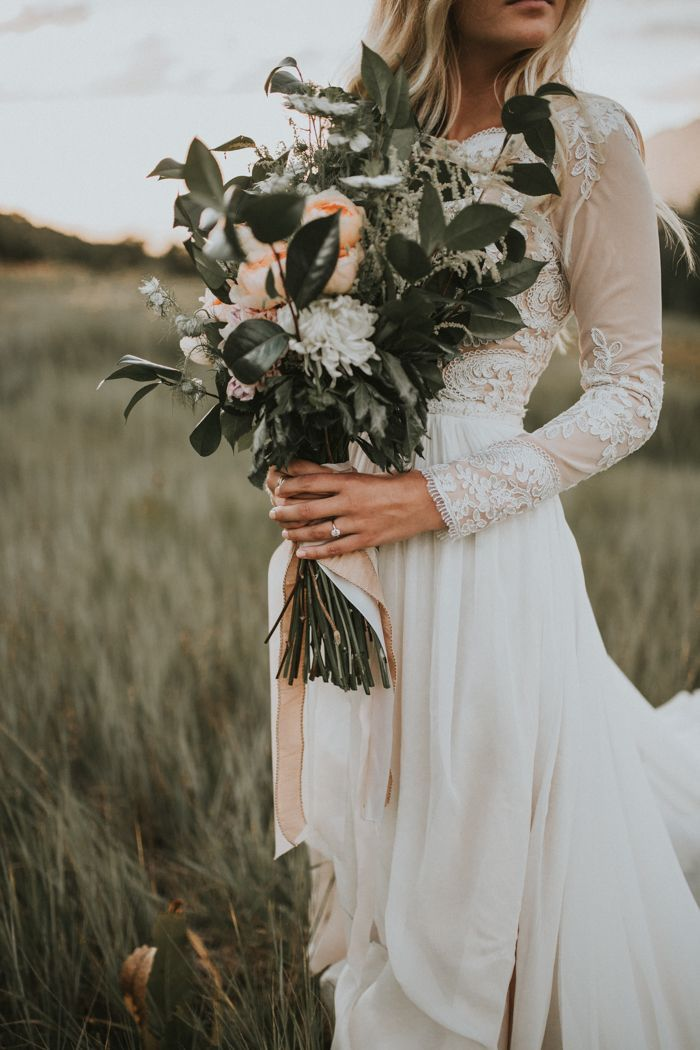Lace-sleeved wedding dress + a matte green and peach wedding bouquet | Image by Autumn Nicole Photography
