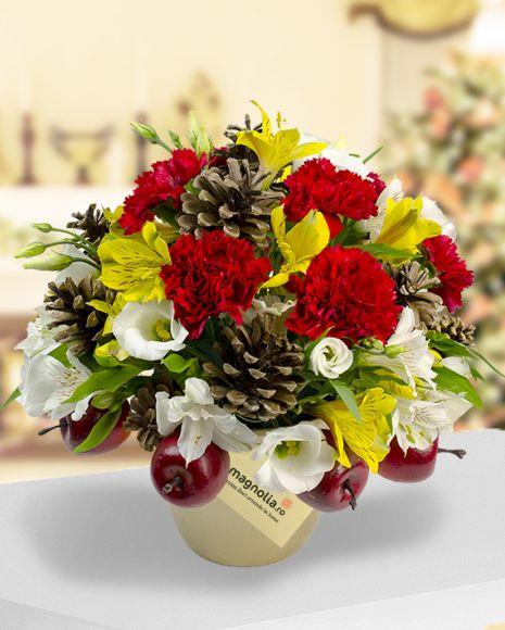 Cadou de Craciun cu Garoafe, Alstroemeria si Eustoma. Accesorizat cu conuri de brad si mere ornamentale, este un aranjament floral potrivit pentru sarbatorile de iarna.
