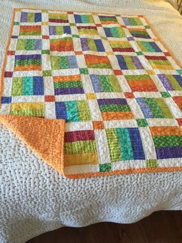 Jelly Roll Baby Quilt.  Do as a large disappearing 9 patch with the 4 corners made from sets of 3 fabric colors, center square being a solid color and the other 4 squares being white (or the same color for each block).  Play with if you need to rotate your 3 color blocks.