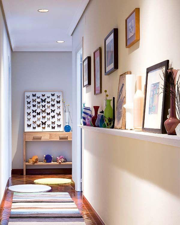 corredor com porta-retratos, vasos e quadros.
