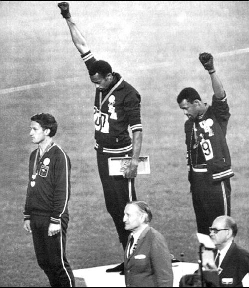 1968 olympics John Carlos (on right), Tommie Smith (centre) and Peter Norman, who wore an Olympic Project for Human Rights badge in support of their gesture. When Norman died in 2006, Carlos and Smith were pallbearers at his funeral.
