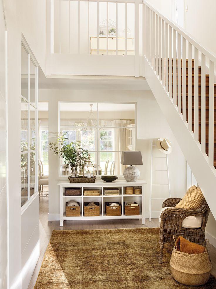 Recibidor blanco con alfombra marrón, sillón de fibra natural, cesta taialndesa, aparador con cestas en los estantes y escalera de pared decorativa 446943