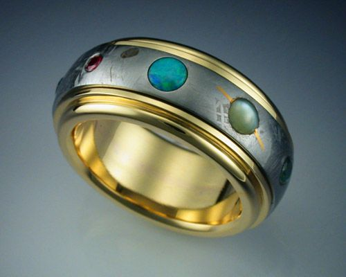 AMAZING solar system ring made out of meteorite. So awesome!    This ring features a complete band of Gibeon Meteorite framed and mounted in an 18k gold band, and set with 9 gemstones representing the planets of our Solar System. Mercury is a rust colored Sapphire, Venus a golden Sapphire, Earth an irradiated blue Diamond, Mars a Ruby, Jupiter an Opal, Saturn a Cats Eye Chrysoberyl with a 24k gold ring, Uranus a green Sapphire, Neptune a blue Sapphire and Pluto a black Diamond.