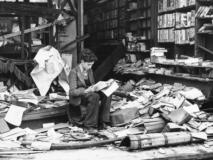 """A boy sits amid the ruins of a London bookshop following an air raid on October 8, 1940, reading a book titled 'The History of London.'"""
