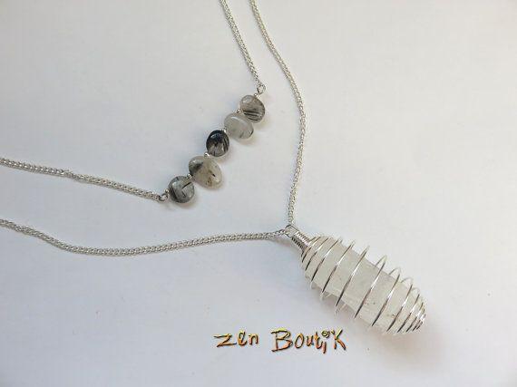 Quartz Rutile avec inclusions de Tourmaline noire Pointe de Quartz Cristal de roche brut en pendentif dans une cage spirale Collier double rang avec chaînes se rejoignant pour un seul fermoir 5 perles de Quartz Rutile Tourmaline Perles polies, arrondies et de taille irrégulière de 12x8mm en moyenne sur une tige de 6cm Quartz cristal de roche brut environ 40x15mm Pendentif cristal avec la cage 50x19.5mm Tour de cou Quartz rutile 45cm Tour de cou cristal de roche 70cm PUMIN029 Livrai...