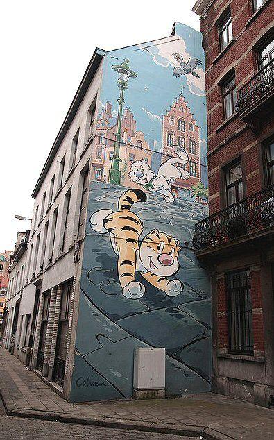 """-rue d'Ophem 24-La fresque murale Billy the Cat d'après un projet original de Colman et Desberg fut inaugurée en juillet 2000. Sa superficie est d'environ 35 m². Réalisation de Georges Oreopoulos et David Vandegeerde de la société """"Art Mural""""."""