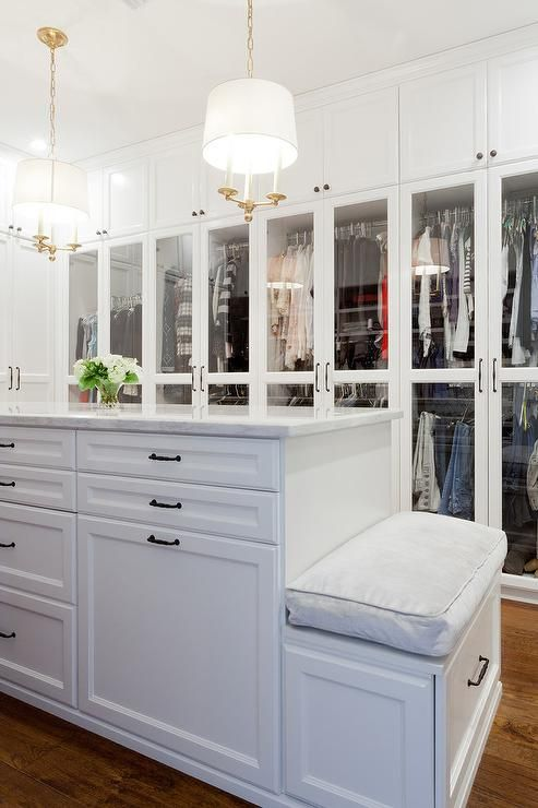 Large, white walk-in closet features two Classic Candle Hanging Lights hung over a white center island accented with oil rubbed bronze pulls and a marble countertop and fitted with a built-in bench topped with a gray cushion.