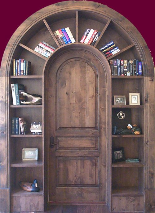 A beautiful arched wooden door with a custom-built bookcase surround