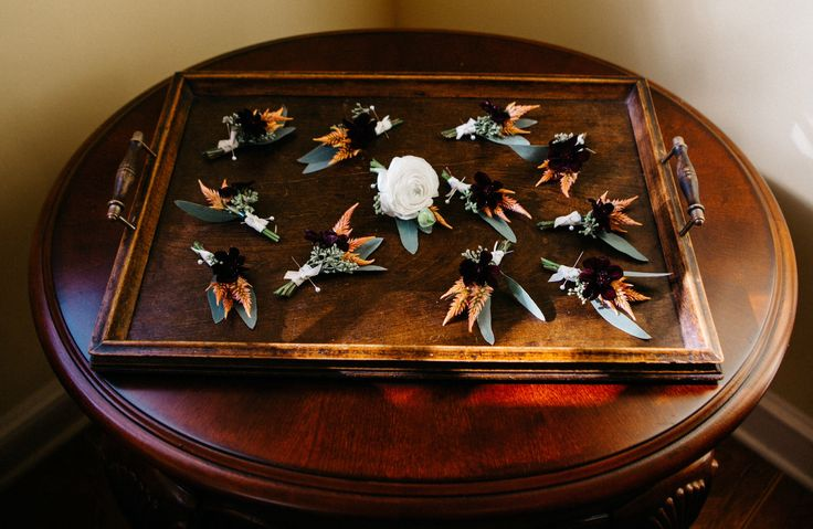 handsome tray of boutonnières for the groom, his groomsmen and ushers. groom's boutonnière made of white ranunculus, peach celosia and seeded eucalyptus. all others made of chocolate cosmos, peach celosia, seeded eucalyptus