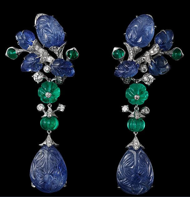 CARTIER HIGH JEWELRY EARRINGS. Platinum, two pear-shaped carved sapphires totaling 25.24 carats, melon-cut emerald beads, cabochon-cut emeralds, sapphire carved leaves, brilliants.