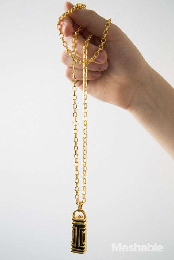 The Tory Burch for Fitbit Fret Pendant Necklace. The Fitbit core pops into the pendant, which is suspended from a chain.