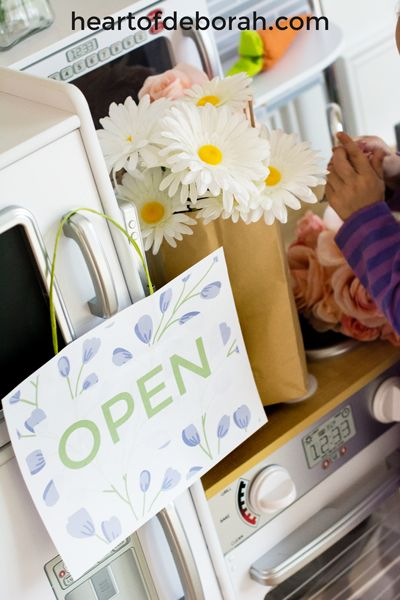 FREE OPEN SIGN! Looking for a spring themed dramatic play center? Create your own flower shop and garden. Kids will love buying and water their floral bouquets. Download the free printables included for an open/closed sign and a flower sign shop.