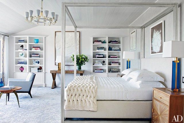 A 1960 Paavo Tynell chandelier from Alexandre Biaggi crowns the master bedroom, which is furnished with a Larrea Studio canopy bed upholstered in a Bergamo fabric; the midcentury T. H. Robsjohn-Gibbings armchair is from Lobel Modern, and the '40s French low table is from Newel. On the far wall is a large artwork by Anthony Pearson, the Roberto Giulio Rida bedside lamp is from Bernd Goeckler Antiques, and the carpet is by Carini Lang.