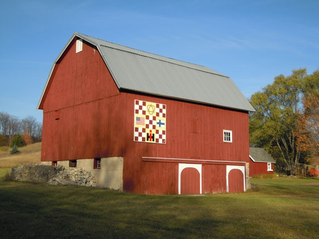 Carl and Suzanne Lehto's 1912 barn is at 15793 Smokey Hollow Rd. on the Old Mission Peninsula, MI. Suzanne designed the quilt to express who they are. The symbol at the top shows their Christian faith; the American flag, their pride of citizenship; the Finnish flag, their heritage; and the IH for International Harvester.