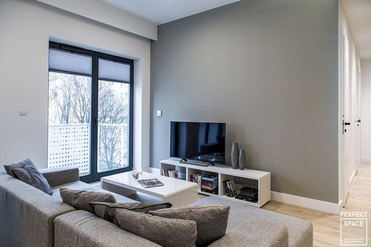 Aranżacja salonu w minimalistycznym stylu. Salon utrzymany w szarej kolorystyce z białymi meblami.