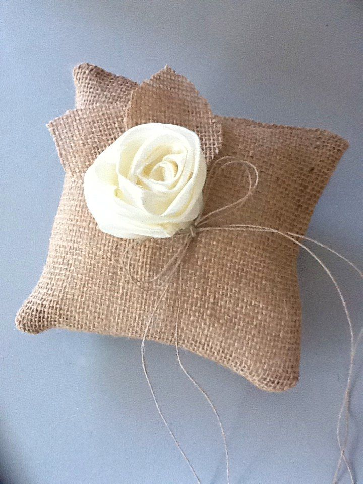 """My charming handmade burlap and satin rose ring bearer pillow is the perfect blend of rustic charm and chic elegance.    Measures approximately 6"""" has a hand made ivory satin flower and natural jute twin to secure your rings for there walk down the aisle.    My Ring bearer pillow coordinates perf..."""