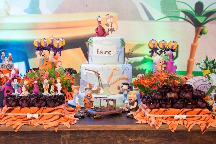 """Na mesa principal da festa de aniversário de um ano com o tema """"Os Flinstones"""", toda a turma do desenho estava presente em bonecos de biscuit da Coisas de Marina (www.instagram.com/coisasdemarinaoficial). A parede atrás da mesa foi coberta com um painel colorido feito de lona"""