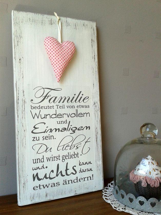 """Weißes Holzschild mit der Beschriftung """"Familie bedeutet, Teil von etwas Wundervollem und Einmaligem zu sein. Du liebst und wirst geliebt und nichts kann daran etwas ändern.""""  Es ist ein schönes..."""