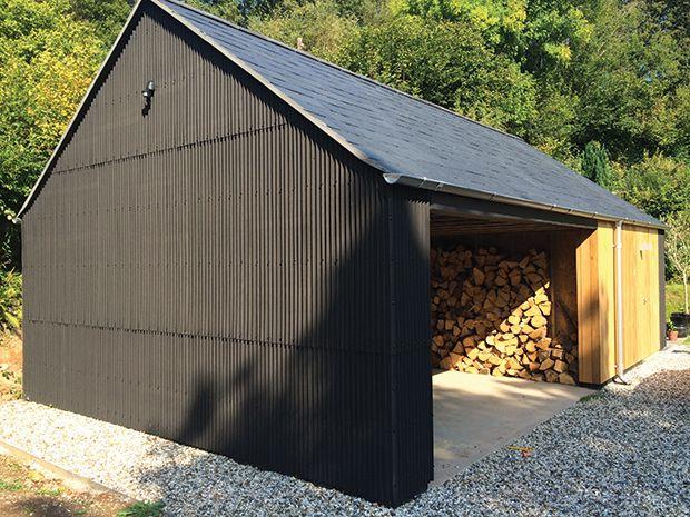 Black industrial style cladding on a log store cum garage