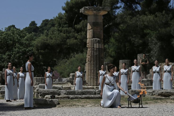 Rio 2016 Olympic Flame is lit in Greece - In perfect weather, the flame was lit by sun rays in the temple of Hera, Olympia, by Katerina Lehou – a Greek actress who played the role of High Priestess, dressed in costume by compatriot and stylist Eleni Kyriacou, a pupil of Alexander McQueen.
