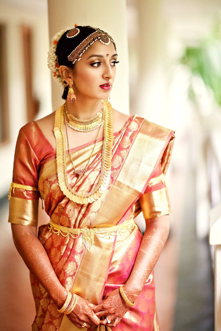 Elegant bride in pink Kanjivaram saree and temple jewellery.