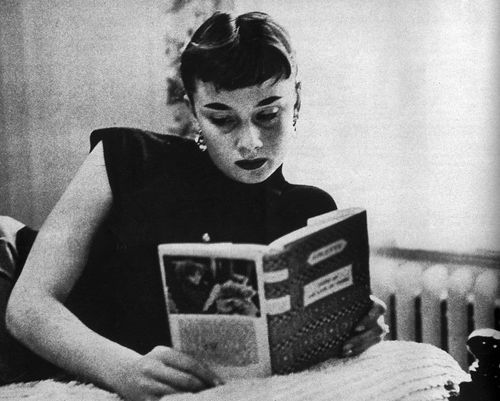 "Audrey Hepburn finds time for a book between having ""Breakfast at Tiffany's""."
