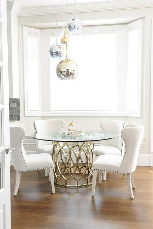 Gorgeous dining room features staggered brass, glass, and chrome pendants above a round glass top dining table surround by white wingback dining chairs with nailhead trim.